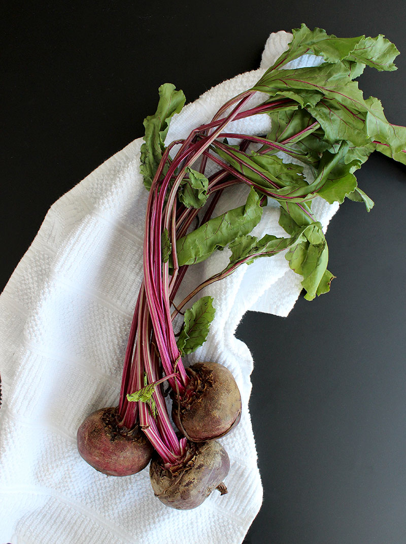 A cluster of beets sits on a white dish towel with a black background.