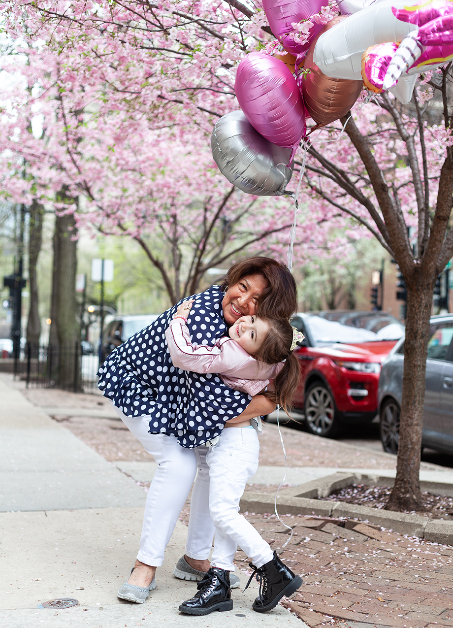 Zelda of Glitter and Bubbles hugs her nanny outside n the sidewalk while holding balloons.