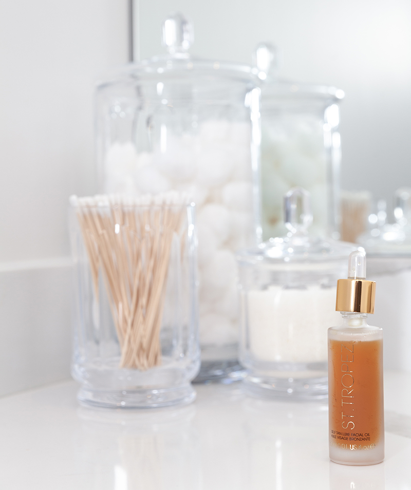 The perfect sunless tanning products sit on a bathroom counter featuring St. Tropez.