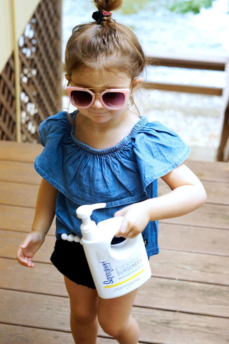 A little girl wearing sunglasses carries SuperGoop sunscreen lotion.