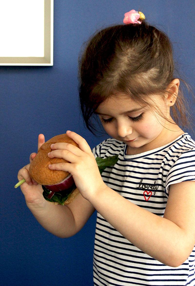 Zelda of Glitter and Bubbles holds a Greek Turkey Burger.