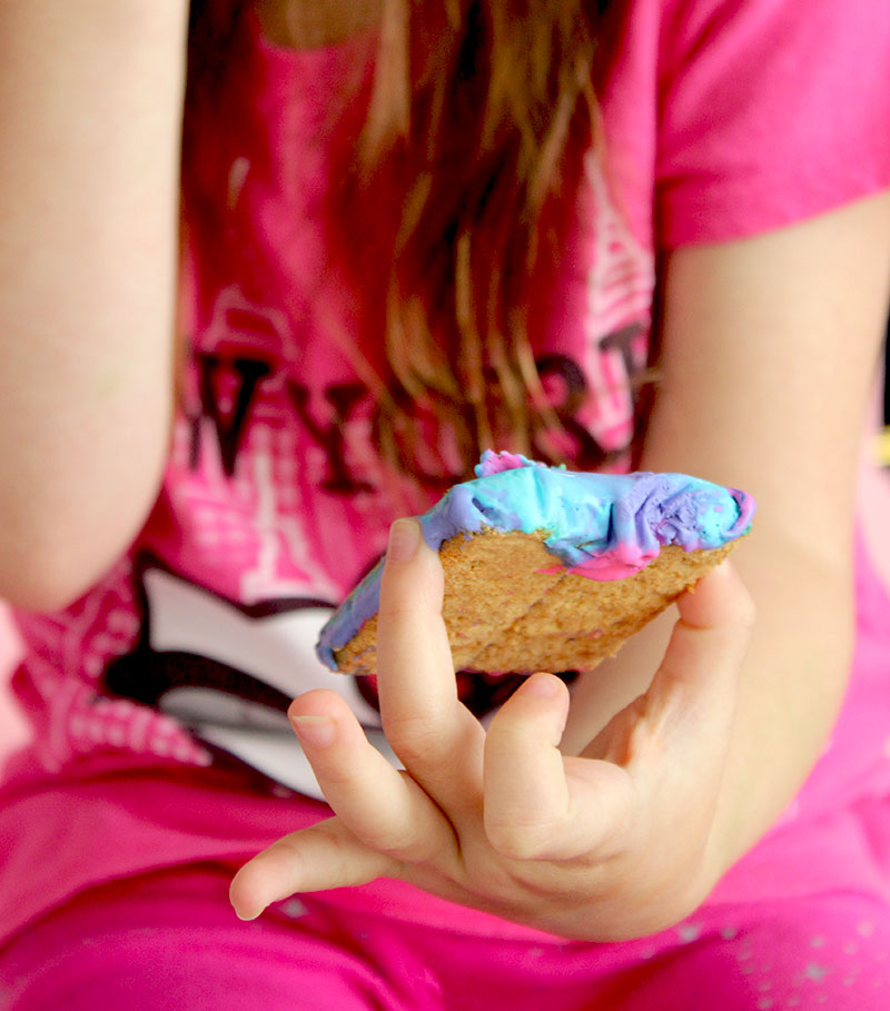 Zelda of Glitter and Bubbles holds a unicorn ice cream sandwich.