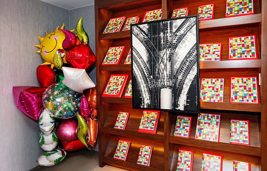 A colorful book wall with balloons.