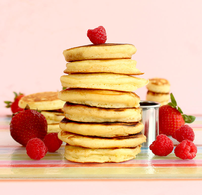 A fresh stack of mini pancakes topped with raspberries and strawberries.