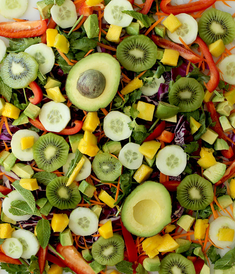 A medley of fruit and vegetables sits on a table ready to be stuffed into spring roll wrappers.