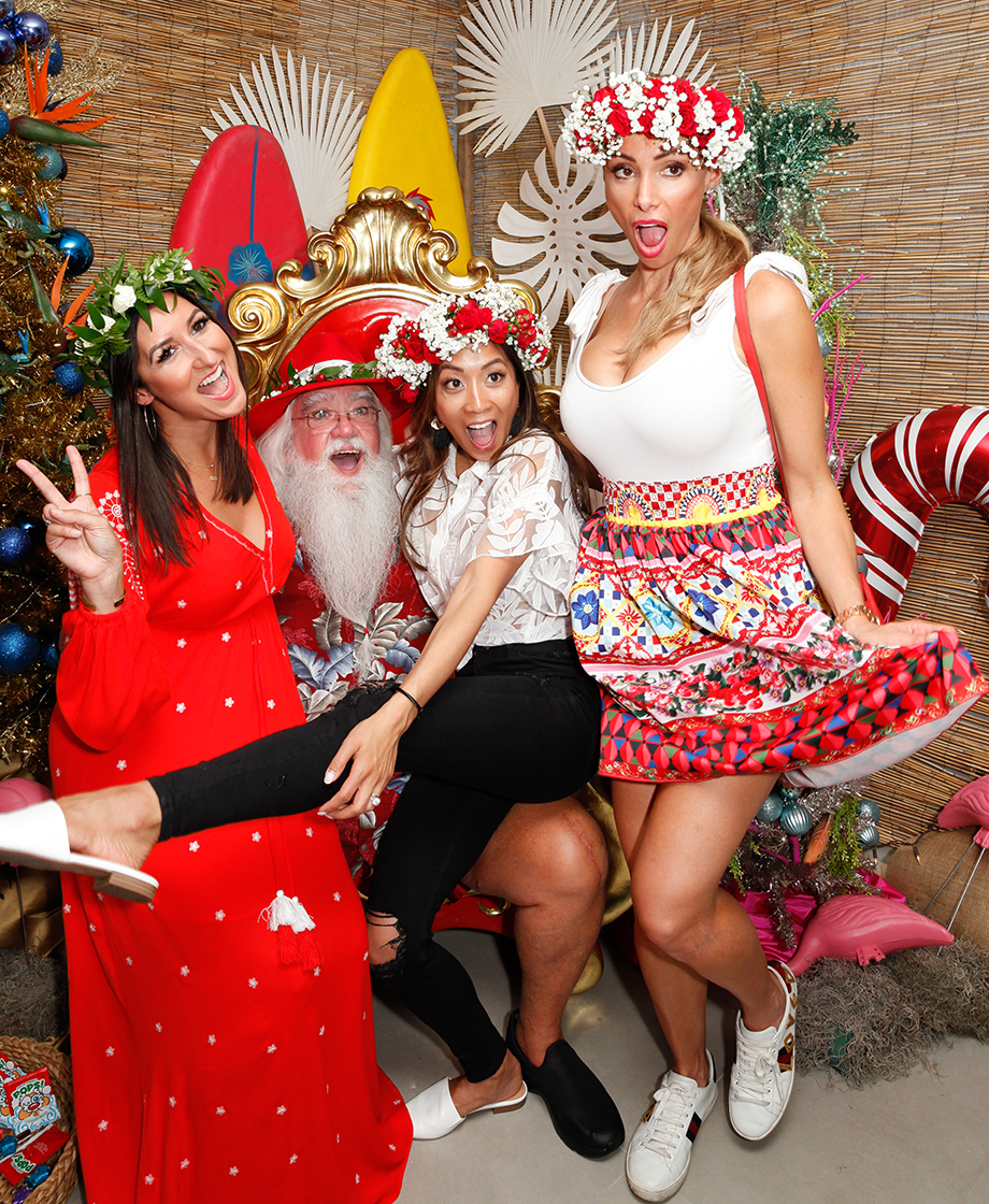 A group of women sit with Santa at the Swissotel.