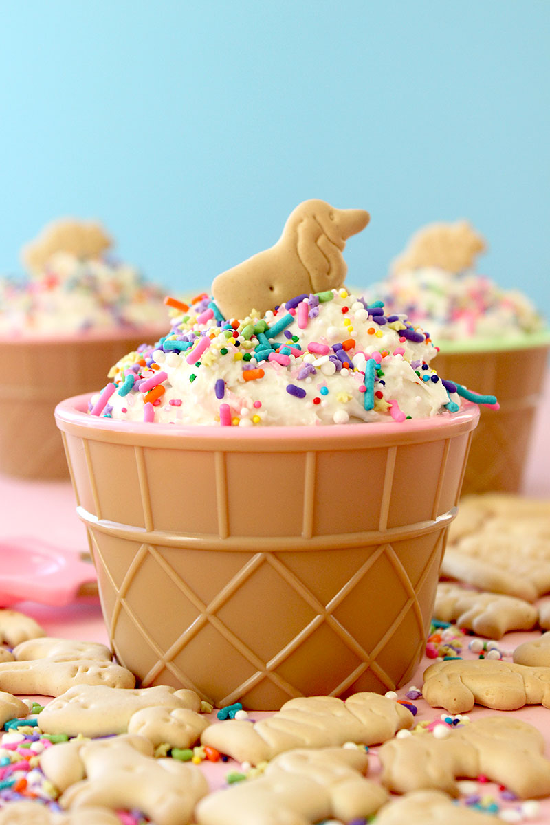 A delicious ice cream bowl is filled with cake batter dip and topped with a cute dog animal cracker on Glitter and Bubbles.