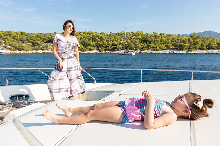 Corri McFadden wears a two piece striped outfit on a boat in Greece while spending time with Zelda.