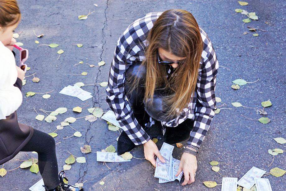 Corri McFadden picks up one hundred dollar bills off the ground.