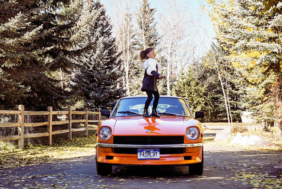 Zelda of Glitter and Bubbles stands on an orange car.
