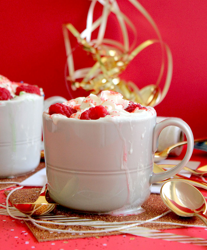 A brownie in a mug topped with whipped cream and raspberries.