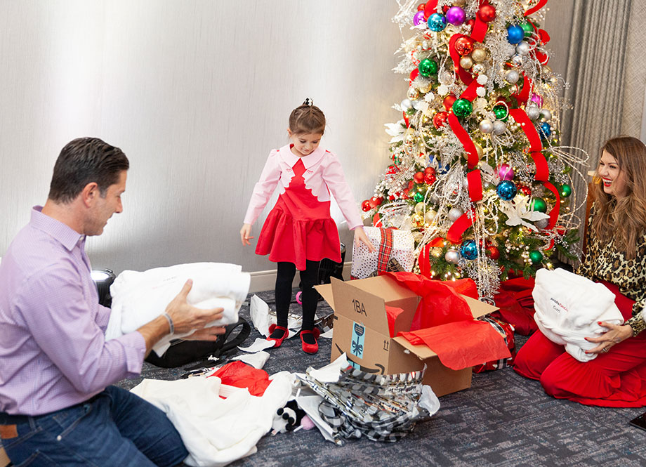 Zelda of Glitter and Bubbles opens gifts with Santa.