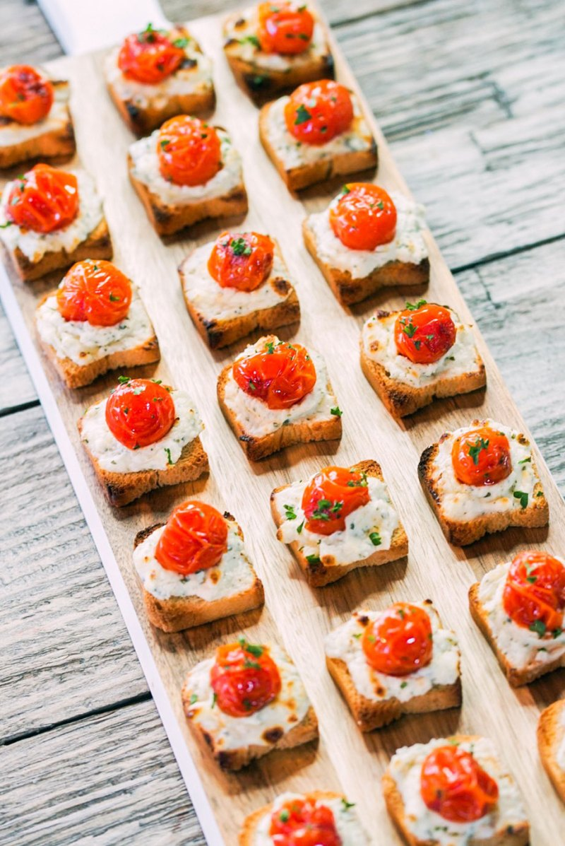 A tiny toast with Alouette cheese and tomatoes.