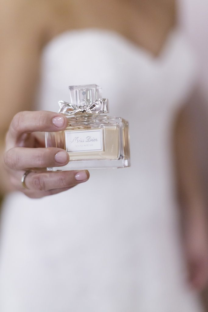 bride holding perfume bottle