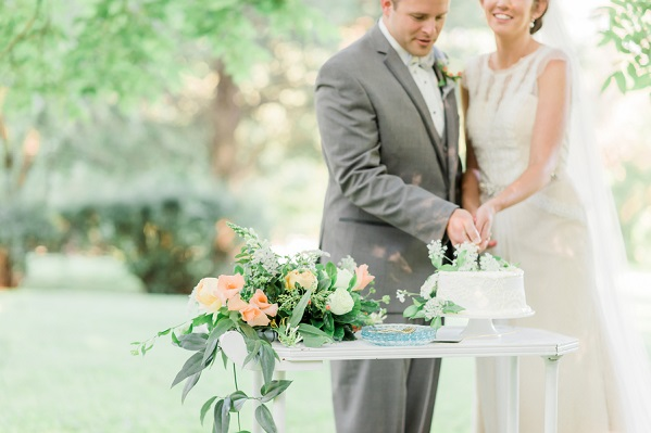bride and groom cutting cake outside on tray