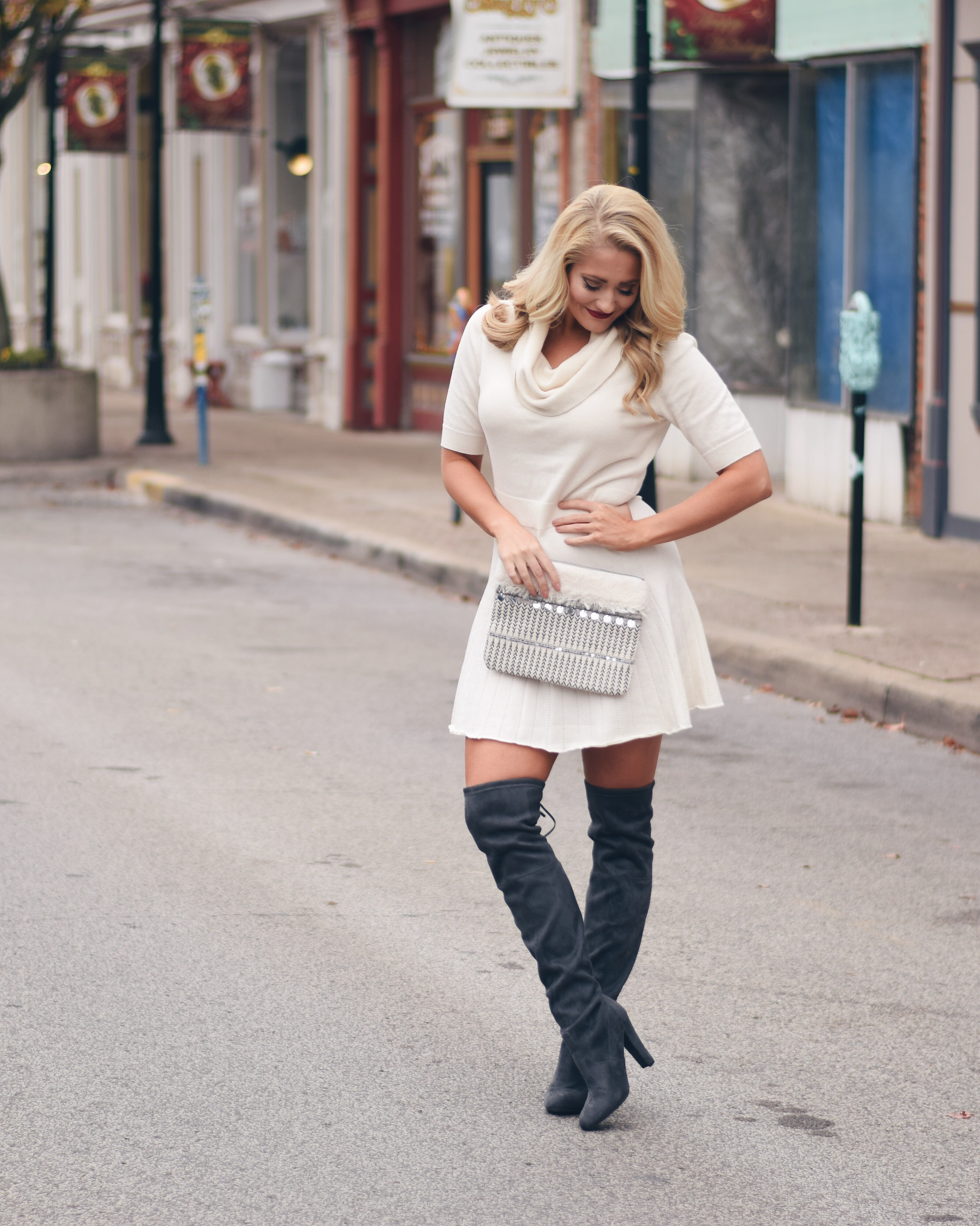 winter white sweater dress with beaded clutch and grey over the knee boots