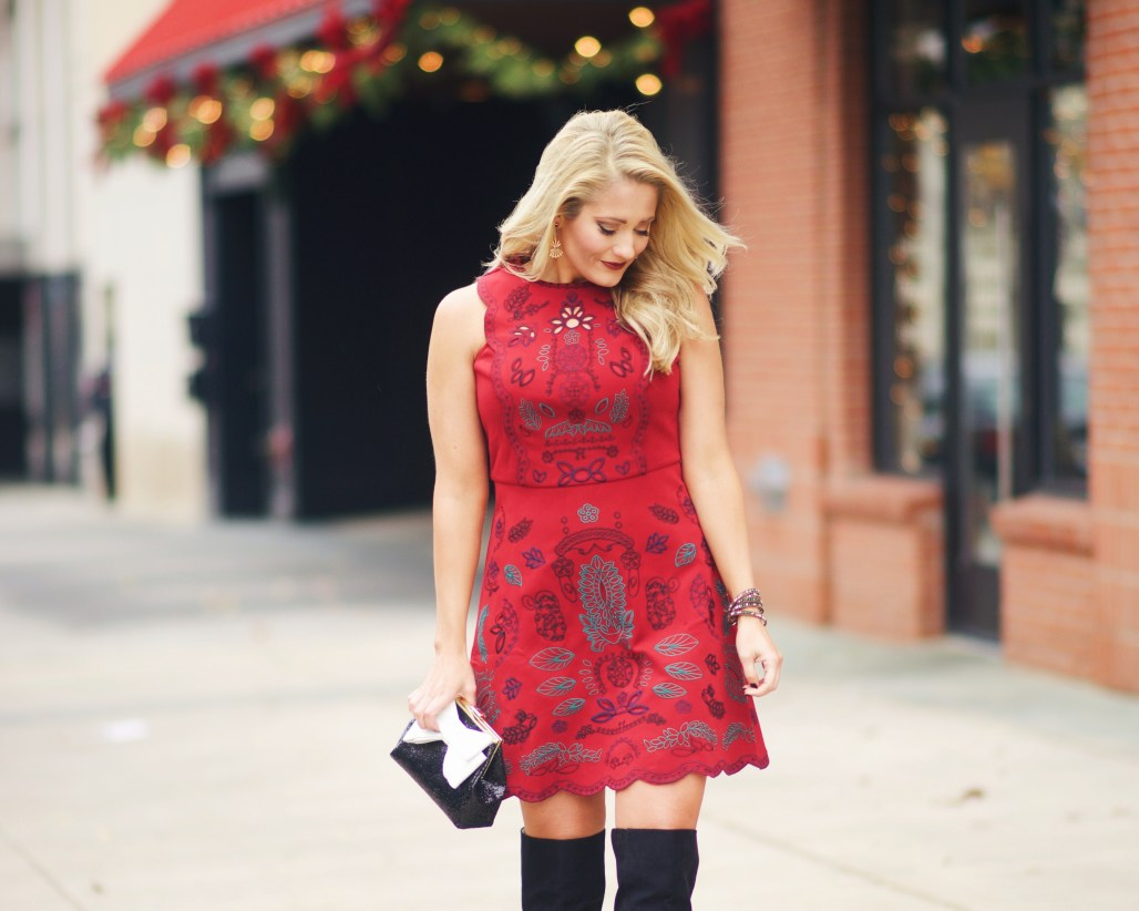 red embroidered dress with black over the knee boots and sequin bow clutch