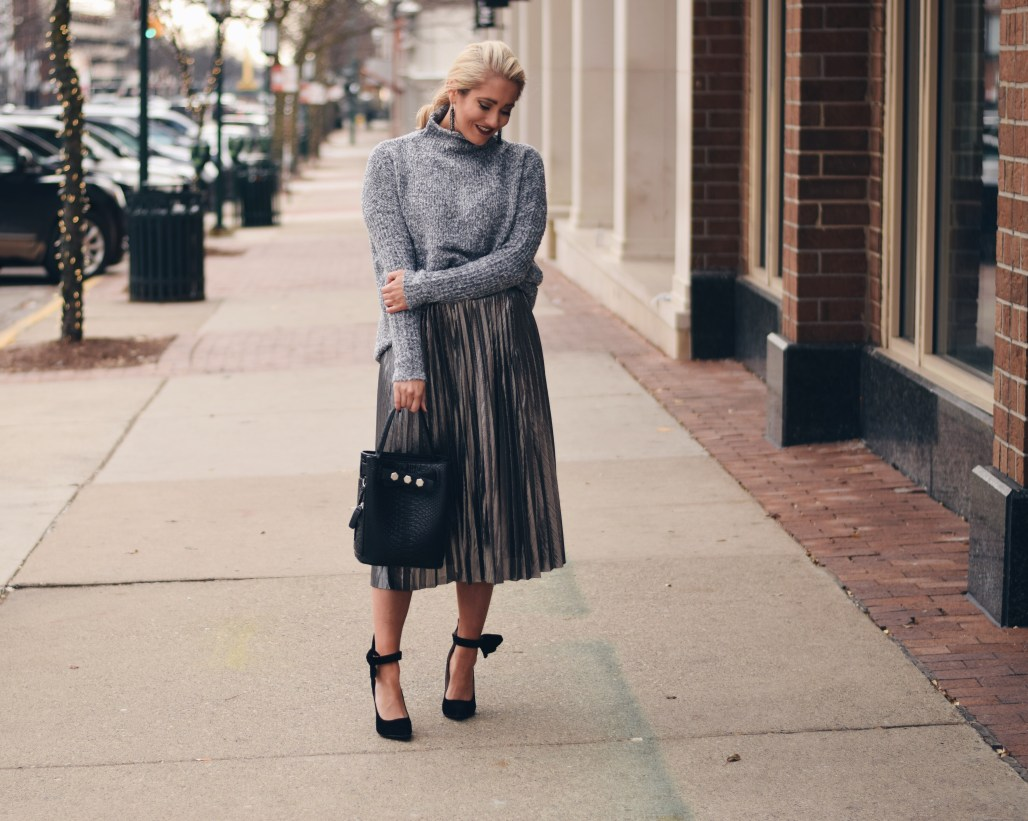 Grey sweater with silver pleated midi skirt and black bow heels