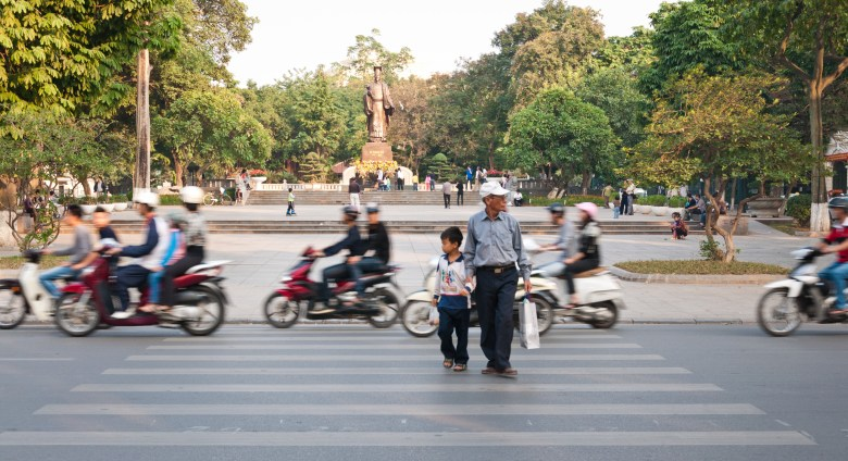 A man and child brazenly cross the street near Sword Lake, in a rare break in the constant swarm of motorbikes. Rush hour in Ha Noi is a real culture shock.
