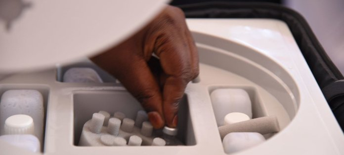 A health worker picks a vial of the AstraZeneca COVID-19 vaccine from a cooler box in Uganda.