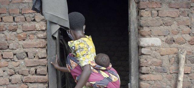 Une jeune fille de 14 ans porte son bébé au domicile de ses parents à Kasese, dans l'ouest de l'Ouganda.
