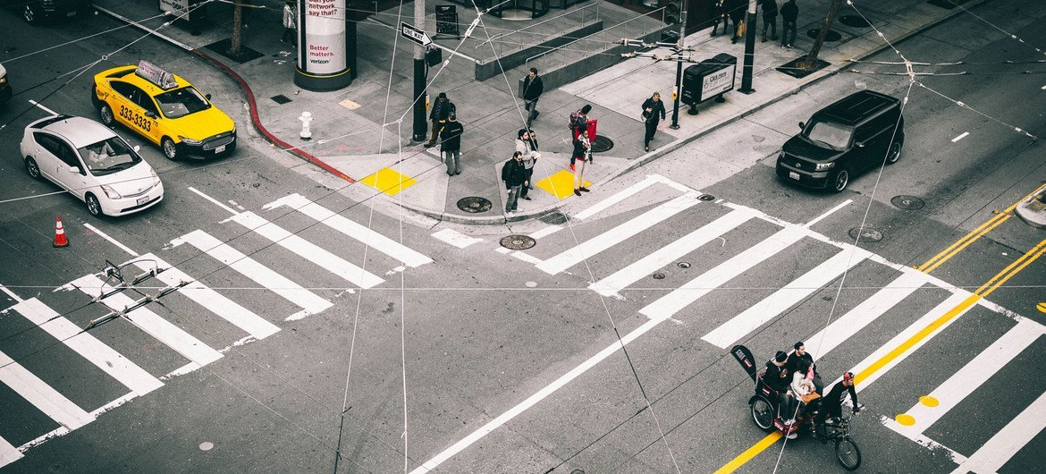 People wait for a light change at a pedestrian crossing in San Francisco, in the United States.