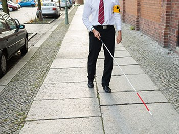 Man with Vision Disability Walking On Sidewalk Holding Stick