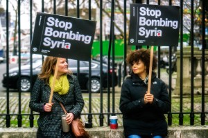 Two people holding anti-war signs.