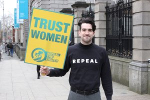 A masculine reproductive rights campaigner holding up a TRUST WOMEN sign