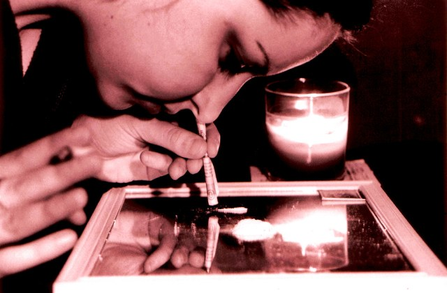 A person snorting a powdery substance off a mirror