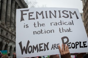 a protest sign: feminism is the radical notion that women are people