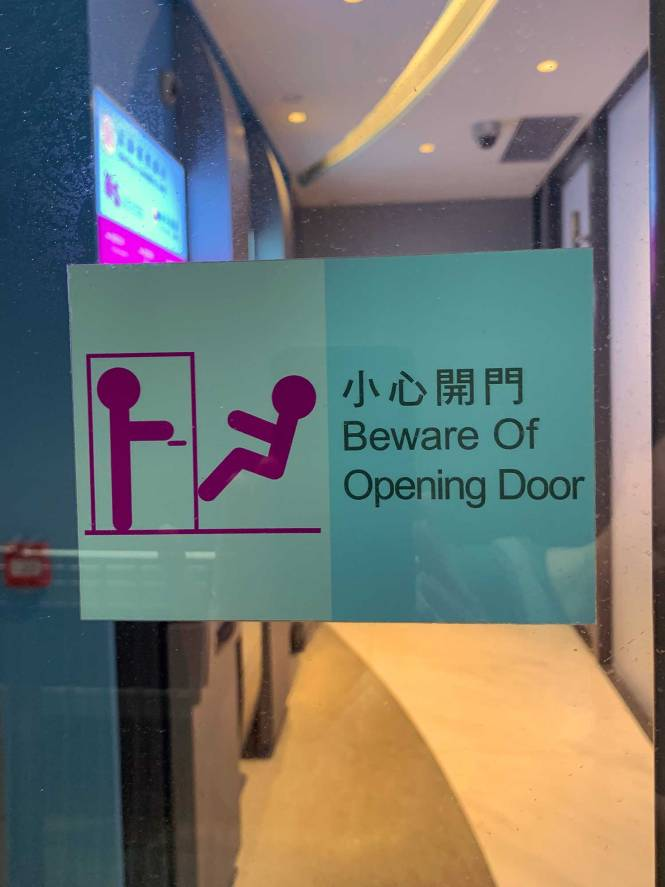"""Beware of opening door"" sign in Hong Kong"