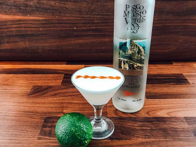 Pisco Sour cocktail with lime and Pisco bottle