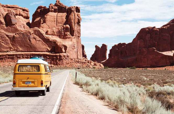 Yellow van driving through red rock formations on a great American road trip