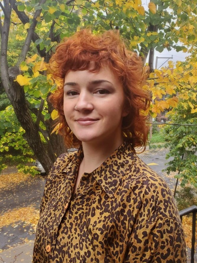 A white women with short curly red hair smiles at the camera. She is wearing a brown and black leopard print silk shirt. The trees in the background are autumnal yellow and green leaves.