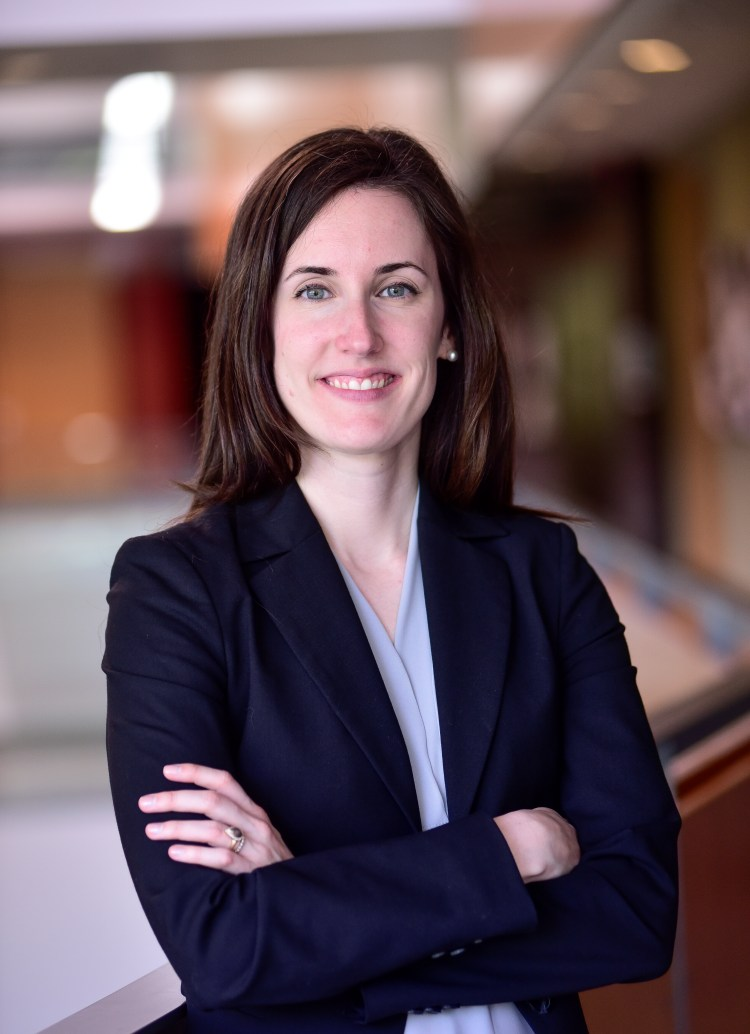 Hilary, a white woman with long brown hair, wears a light blue shirt and navy blazer, and smiles at the camera.