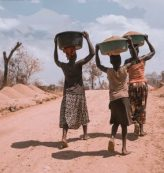 three women carrying basin while walking barefoot