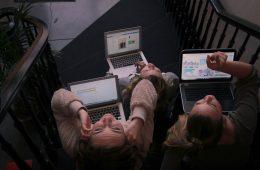 लैडर पर बैठकर लैपटॉप का उपयोग करते ह�� तीन व�यक�ति
