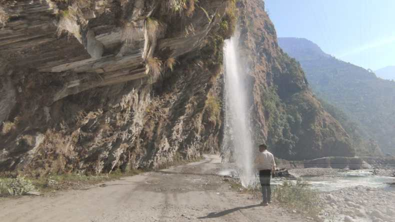 Picturesque: Jauljibi-Madkote Road under Mighty Himalayan Range through a Waterfall