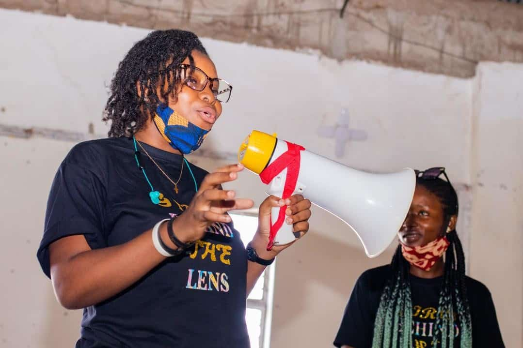 Woman wearing a 'Girls behind the lens' t-shirt speaks into a megaphone