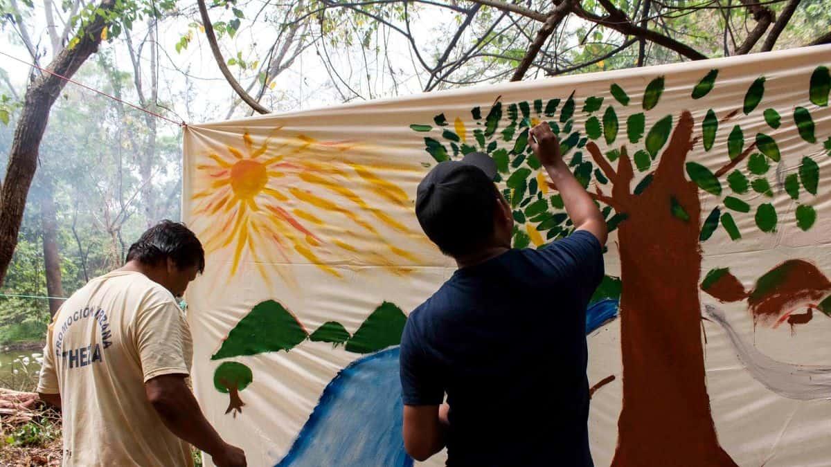 Two men paint a landscape scene on an outdoors canvas