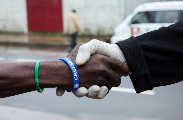 A man from Liberia wears a protective glove as he shakes hands with another in the capital Monrovia, July 28, 2014. Many in the city have started wearing gloves in an attempt to avoid contracting the virus. EPA/Ahmed Jallanzo