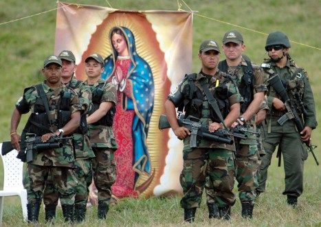 Colombian paramilitaries from the AUC stand guard during a ceremony to lay down their arms in northwest Colombia in 2005. (AP Photo/Fernando Vergara)