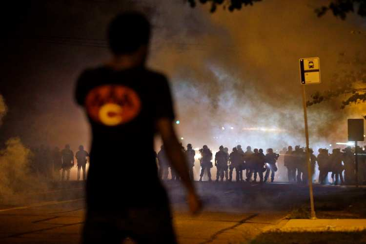 A man watches as police walk through a cloud of smoke during a clash with protesters, Aug. 13, 2014, in Ferguson, Mo. (AP Photo/Jeff Roberson)