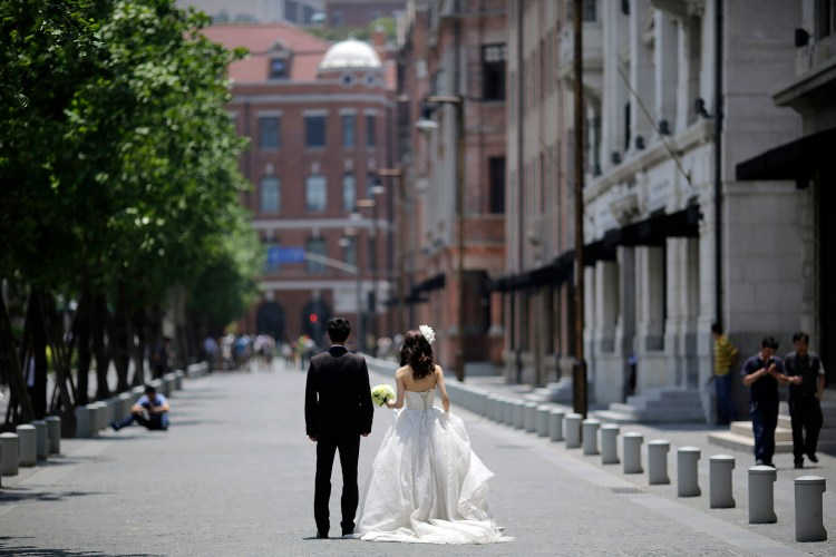 A couple waits for a wedding photo session in Shanghai in 2012. (AP Photo/Eugene Hoshiko)