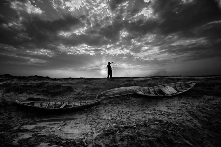 Abu Kalam, a Rohingya refugee in Bangladesh, points across the Naf River to Myanmar where his mother lives. (Saiful Huq Omi)