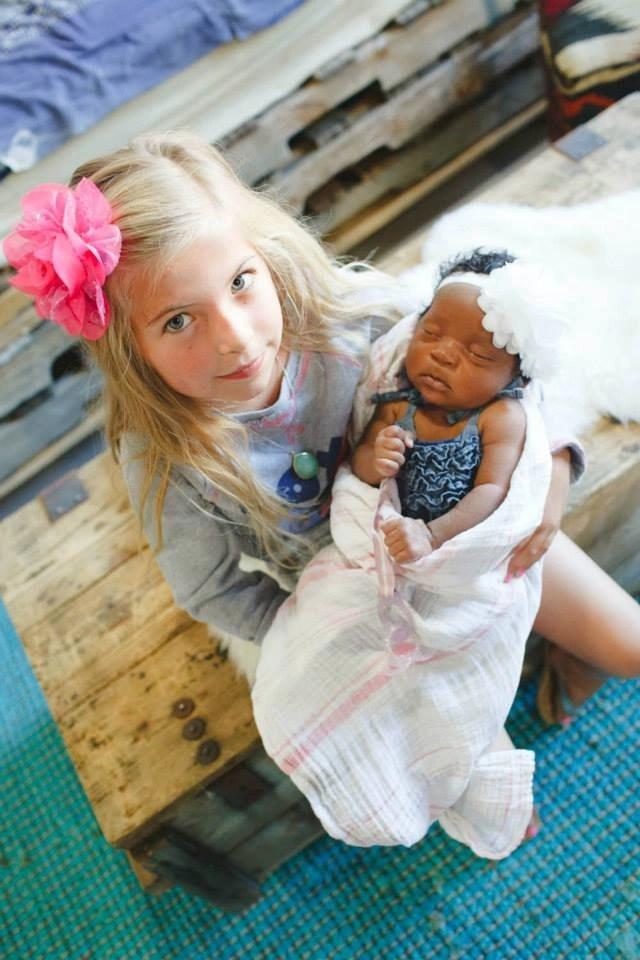 Transracial adoptive sister holding newborn sister