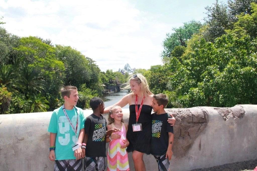 Transracial adoptive family laughing with mom on bridge at animal kingdom