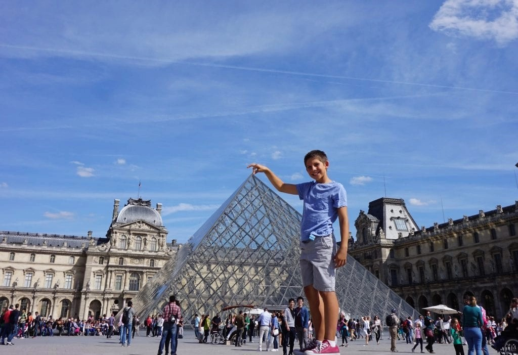 Boy standing next to Louvre in France as if he was touching the top with his finger