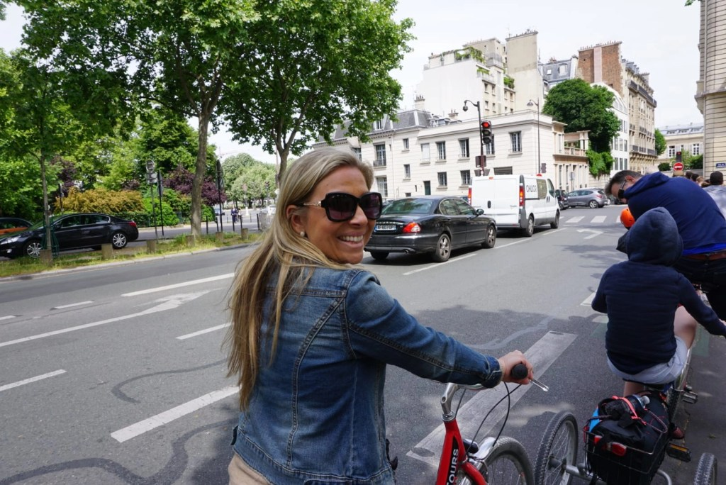 Mom smiling as she rides a bike through Paris